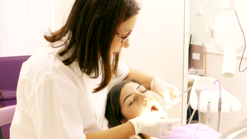 Dentist at work in dental unit with a young woman patient closeup   Shutterstock HD Video #32936479