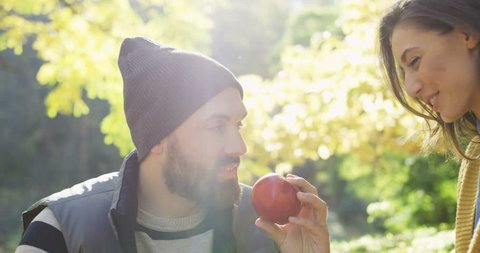 Close up of happy young couple in love sitting in the park. Man biting an apple and woman eating a grape. Sunny autumn. Outside. Portrait