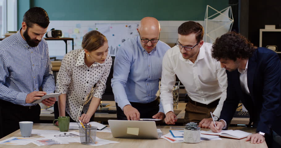 Young group of business workers standing around a table with documents, charts, graphics and financial reports and consulting cheerfully with their boss about startup. Inside of modern office space | Shutterstock HD Video #32941639