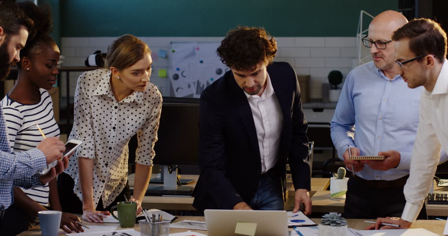 Young business team of mixed races office workers analizing the data and discussing a new startup project with a boss. The table with laptop, documents, charts, graphics and financial reports. Inside | Shutterstock HD Video #32941666