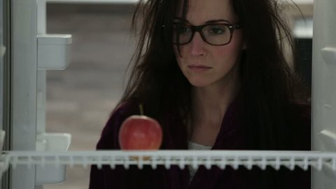 tired woman opening fridge in the morning searching for food annoyed to find only one apple