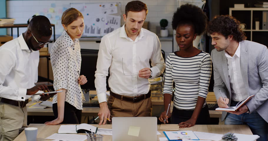 Young multi-ethnical business team working on a project and their boss giving them tasks in the cozy modern office. Planning a startup. Inside | Shutterstock HD Video #32952358