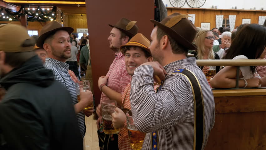 MUNICH, GERMANY, SEPTEMBER 16, 2017: Group of drunken men in national costumes inside a large beer pub with beer mugs in their hands celebrate and have fun on Oktoberfest festival. Bavaria, Germany