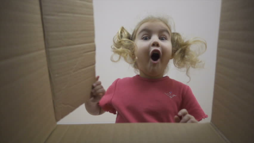 A little girl looks in the box, is surprised and happy to receive a surprise. The child opened a box with a gift.Slow Motion