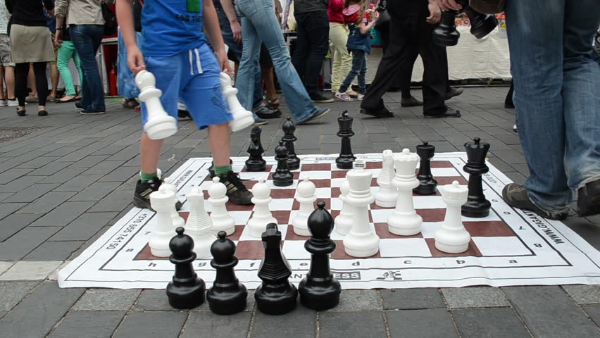 Kids play chess game in city street event with huge figures on September in Vilnius.