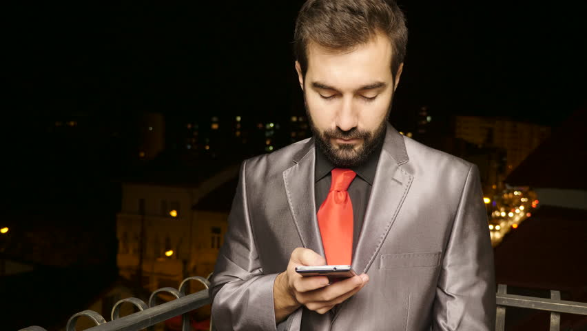 Happy businessman at the balcony browsing on the smartphone in the night. Communication and mobility | Shutterstock HD Video #32988295