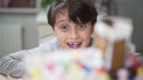 Happy and proud little boy kid looking at his colorful Christmas gingerbread house rotating 360 degrees in the kitchen during winter holidays. Focus changing.