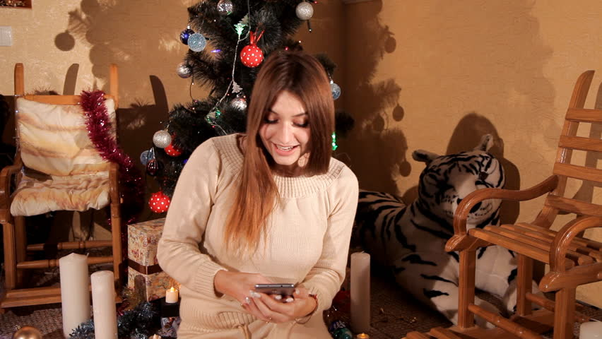 In the festive New Year's environment, the girl uses a mobile phone | Shutterstock HD Video #32991496