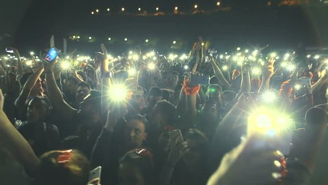 MONTENEGRO - KAMENOVO BEACH, 20.05.2017 - People hold up their cell phones with the lights at a concert