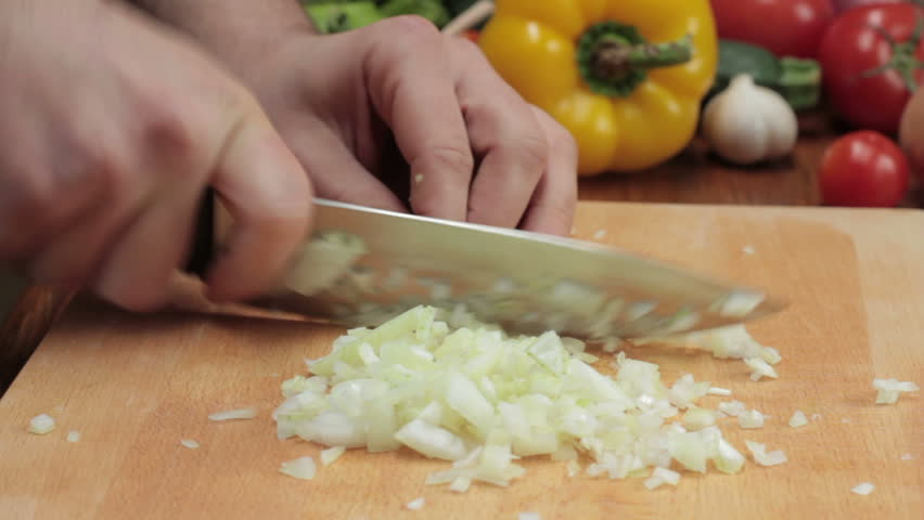 Chef cutting up an onion with a knife, tracking shot