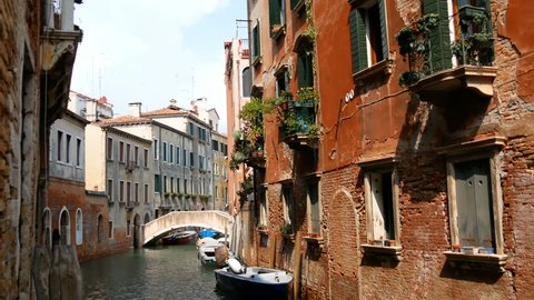 Vintage old dilapidated walls of red brick with glass windows and pots of flowers on the windowsills. A cozy quiet Venetian canal
