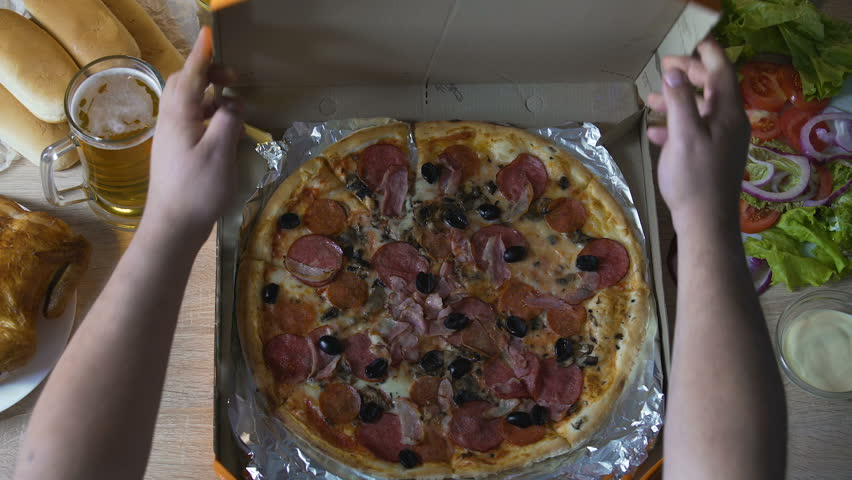 Male's hands opening box with huge oily pizza, going to overeat, greediness