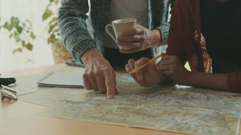 Senior couple with map at home, making plans.