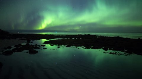 Aurora borealis and stars reflecting in calm ocean tidal pool water Iceland prores