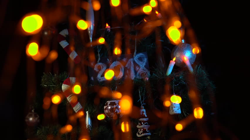 Plate numbered 2018 on a Christmas tree among toys and yellow electric lights, New Year's background. | Shutterstock HD Video #33030634