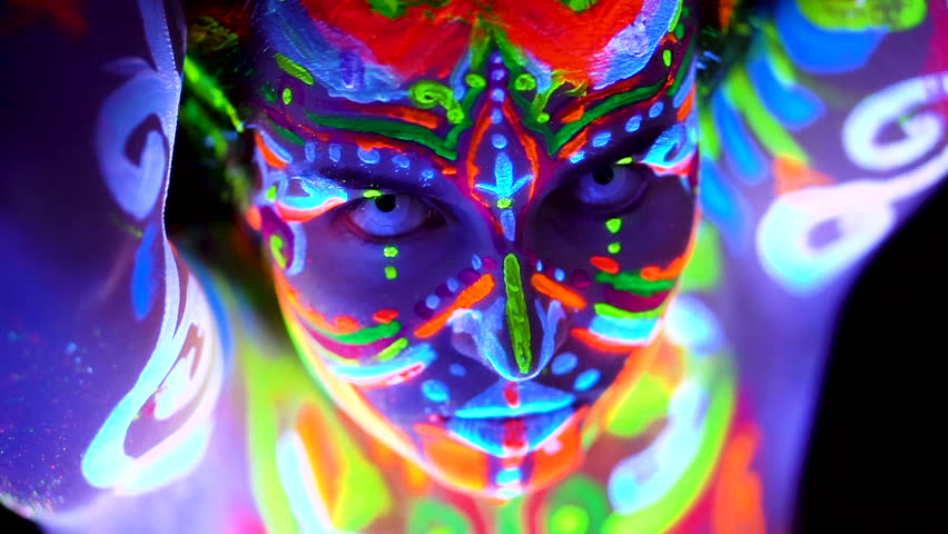 Close-up Emotions of young bodyarted avatar girl in ultraviolet light. Face of woman in color light.