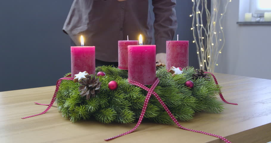 Third Sunday of Advent - a young woman is lighting the third candle of the advent wreath - ProRes