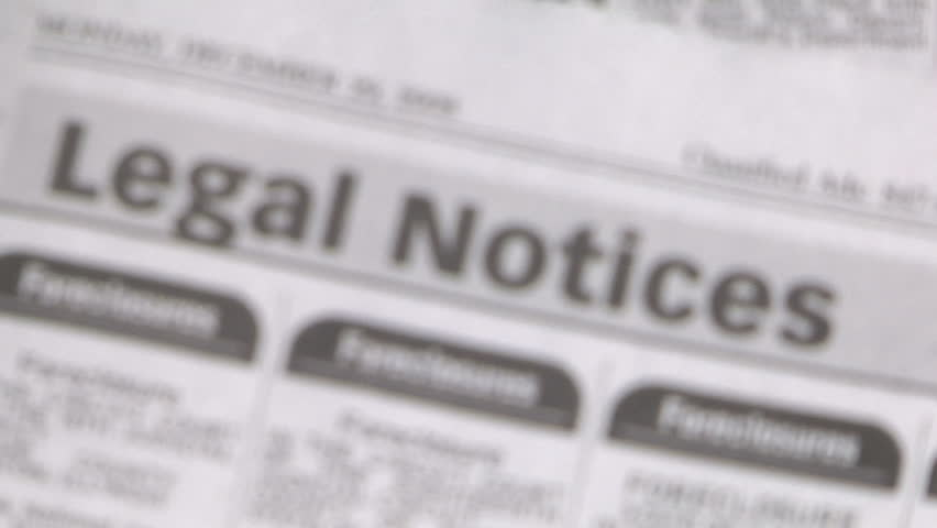 magnifying glass focuses on the foreclosures section of the newspaper