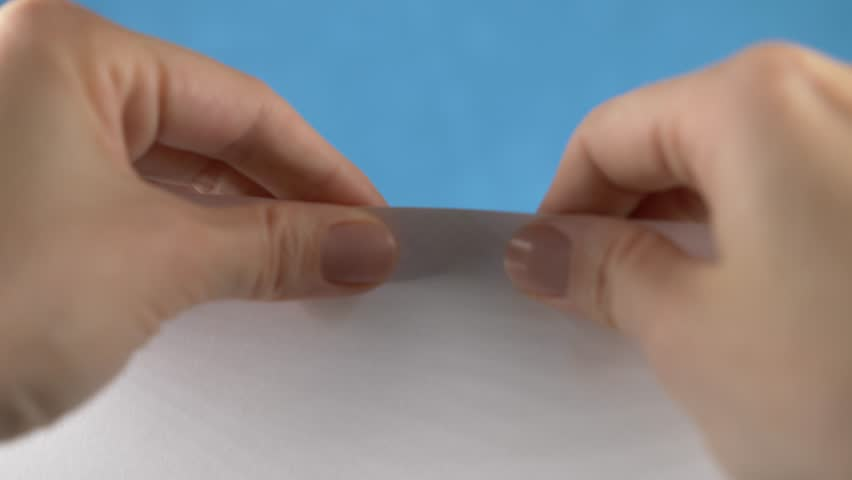 Hands tearing paper sheet, closeup on a turquoise background. 4k, slow motion   Shutterstock HD Video #33078979