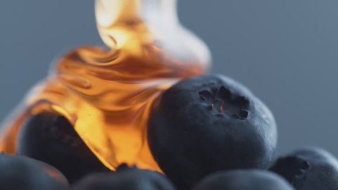 Thick honey dripping over blueberries. Shot with high speed camera, phantom flex 4K. Slow Motion.