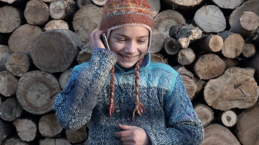A village boy talking on a smartphone near the wood. Portrait of a child govrschego on your mobile phone 4K video. | Shutterstock HD Video #33094060