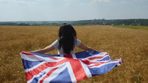 Woman in jeans shorts runs on ripe wheat field with UK flag - Union Jack