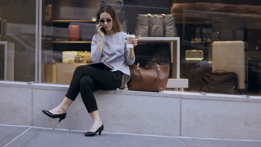 Coffee break of young stylish businesswoman. Happy female sitting near the shop-window and using smartphone, talking.