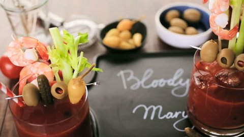 Bloody mary cocktail garnished with olives, pickles, and cocktail shrimp.