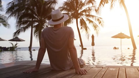 relaxation on the beach, young man tourist enjoying beautiful sunset in luxury hotel, vacation