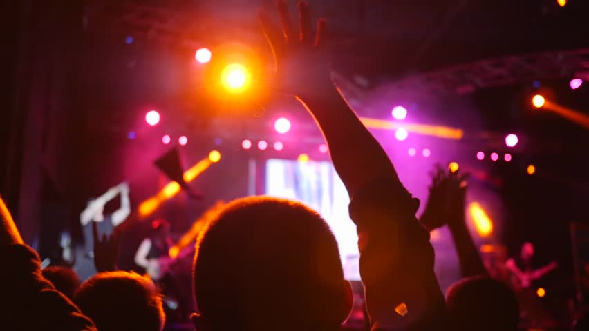 crowd of people with hands up on background stage illuminated by floodlights at concert in night