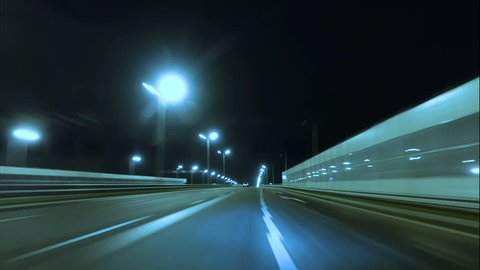 Time lapse of driving a car in the city at night time. POV. Hyper laps in the evening downtown.