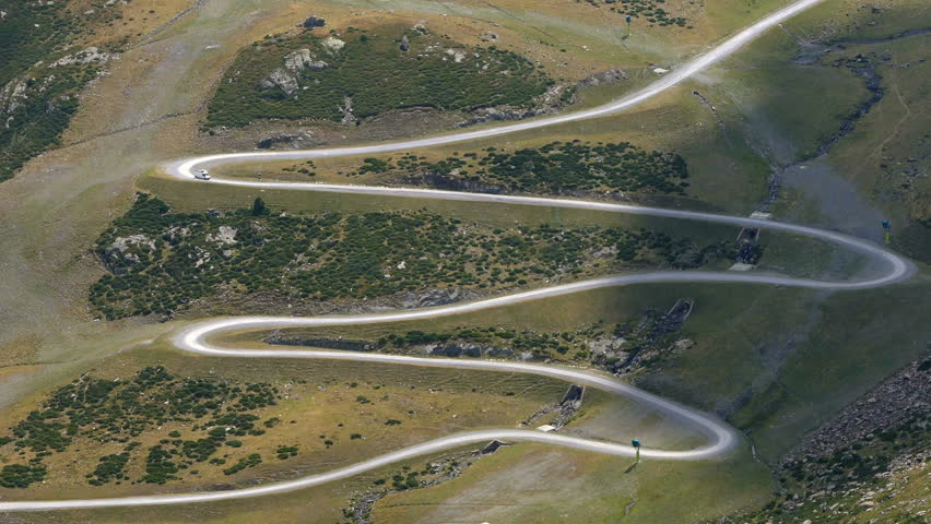 Very sinuous mountain road. Where a van goes at full speed, and with movement of sunlight and the  shadow of the clouds. Aerial view.Time lapse