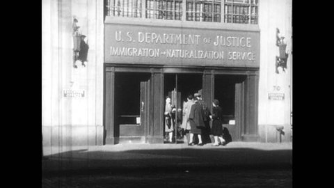 1940s: People enter government building. Man and women approach desk and raise hands. Man behind desk look through papers and speaks. Man and women listen. Judge and crowd in courtroom stand.
