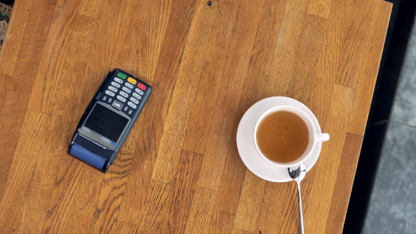 A view from above on a coffee cup and a smartphone during an NFC payment.