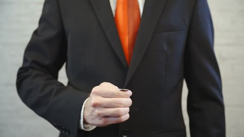 Flipping the coin and catching on top of hand 4K. Long shot of businessman with a red tie from shoulders to waist and hands holding a coin in focus. Shoot on an office wall background.