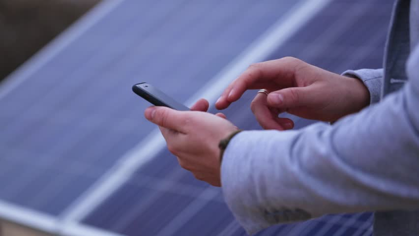 Close-up of a hand with a phone on a background of solar panels | Shutterstock HD Video #33227974