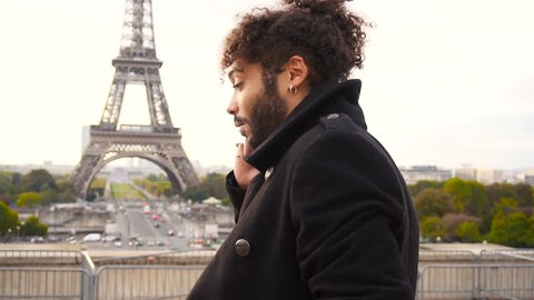 Half Italian and Nigerian man making call with modern smartphone close to Eiffel Tower in slow motion. Young male person has black curly hair, nice smile and earing, wears black coat. Concept of new