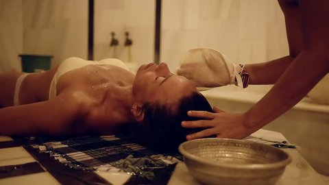 masseur is cleaning face skin with kese bath mitt of client woman, is lying on a table in a hammam