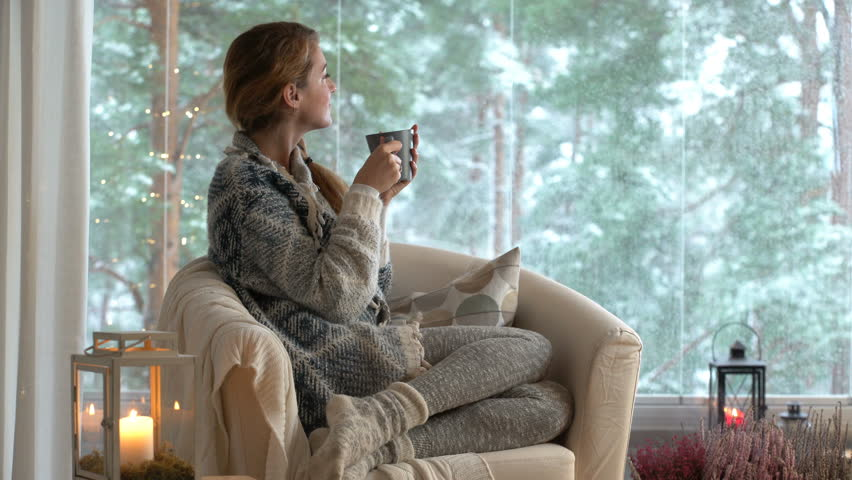 Cozy winter lifestyle. Young happy woman drinking cup of coffee wearing knitted sweater sitting home by the big window with winter snow tree background