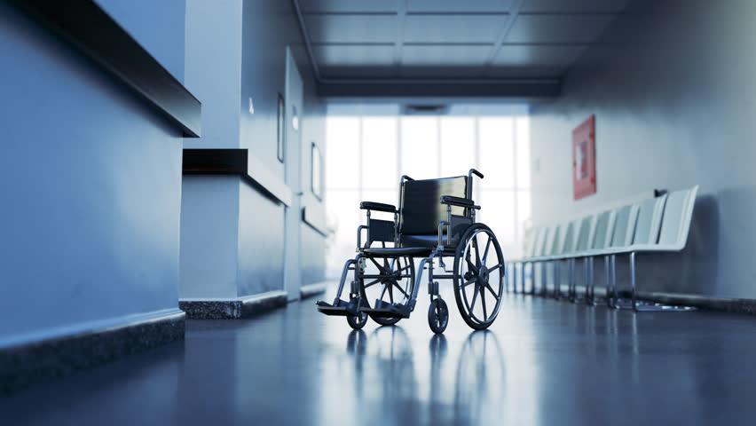 03006 Standard manual wheelchair in empty hospital corridor. Zoom in camera.   Shutterstock HD Video #33252289