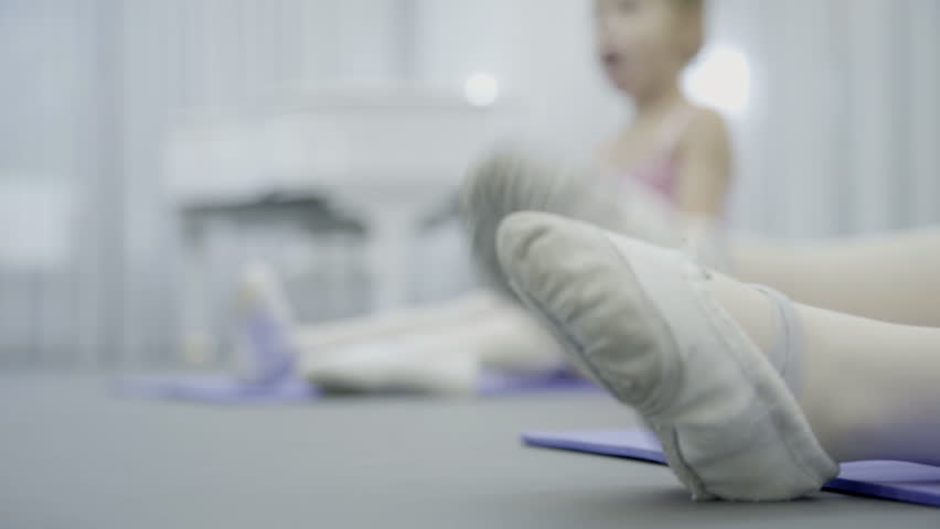 A close up of girl feet in gymshoes while doing the swing sideward during the ballet class. The little dancer sits on the flour and her friend is rightward. The children turns their left legs left   Shutterstock HD Video #33260446