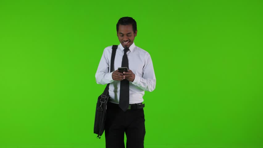 Texting or using an app in a phone while walking by a young businessman over a green screen. Medium frontal shot. | Shutterstock HD Video #33260899