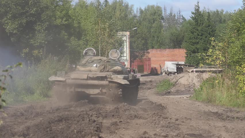 Military tank driving on road on background destroyed building slow motion. War tank driving on dirty road on bakground brick building