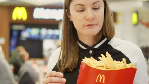 MOSCOW, RUSSIA - CIRCA November 2017: Hungry teen girl eating french fries at McDonald's food court. Holding red paper box with M logo at fast food restaurant