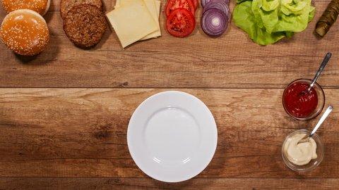 Hamburger ingredients assembling a delicious burger - top view, stop motion