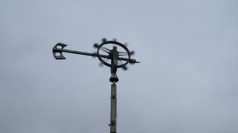 Weather vane in moving cloud background.