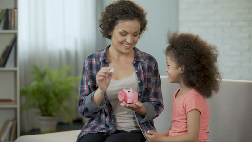 Mom and daughter throwing coins into piggy bank, saving money for presents | Shutterstock HD Video #33287689