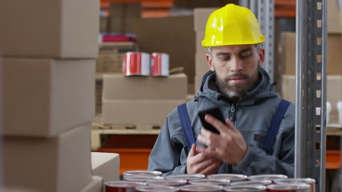 Zoom out with slowmo of bearded male warehouse worker in hard hat stocking cans of paint and calling something on mobile phone