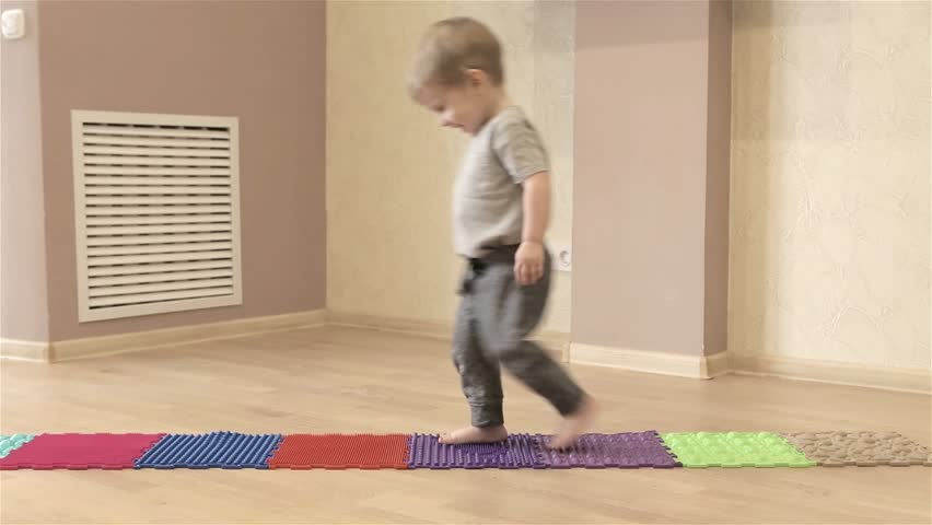 Small 2 Years Old Child Walking On An Orthopedic Mat Ortho Is A Good