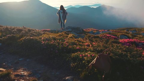 Back view of fit woman in boho look practicing yoga while standing on the mountain top, enjoying the moment and observing the distant hills, forest. Harmony, relaxation, happiness.